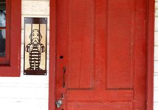 Mr. Monopoly Man shown wearing a jail uniform by a locked red door. Rich Uncle Pennybags is the mascot of the game Monopoly. He is depicted here behind bars in royalty free stock photo
