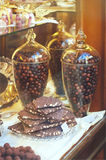 Rich variety of chocolates in big glass jars and candies in disp Royalty Free Stock Photography
