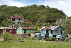 Rich versus poor. A wealthy merchant building his new house in Roatan, Honduras, while his neighbors live in shacks made out of scrap lumber Stock Image