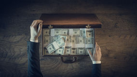 Rich vintage businessman with lots of dollar packs Royalty Free Stock Photography
