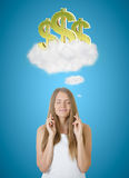Rich and wealth concept. Attractive young european woman with crossed fingers thinking about golden dollar signs in clouds on blue background. Rich and wealth stock photo