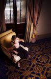 Rich Wealthy Woman Sitting In Upmarket Hotel. Rich And Wealthy Woman Sitting In A Upmarket Hotel Armchair During A Travel Trip To A 5 Star Holiday Resort Royalty Free Stock Photography