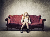 Rich woman. Beautiful rich woman sitting on an old velvet sofa stock photos