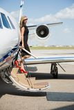 Rich Woman Disembarking Private Jet Stock Image