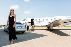 Rich Woman In Elegant Dress At Airport Terminal. Full length of rich women in elegant dress standing against limousine and private Royalty Free Stock Image