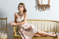 Rich woman on luxury sofa. Rich woman with aristocratic style lying on antique sofa in aristocratic room and looking in camera. Wearing elegant pink dress and stock photography