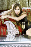 Rich woman near a coffee table. Beautiful young rich woman near a coffee table with glass of fizz stock photo