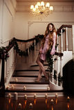 Rich woman on staircase with a candle Stock Photo