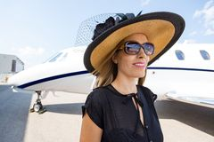 Rich Woman Standing Against Private Jet Royalty Free Stock Images