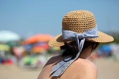Rich woman during tanning with straw hat on the beach of tourist stock photography