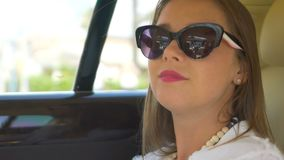 Rich woman travelling by car on back seat of expensive comfortable limousine. Stock footage stock video