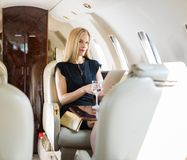 Rich Woman Using Tablet Computer In Private Jet. Portrait of rich mid adult woman using tablet computer in private jet royalty free stock photos