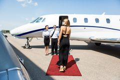 Rich Woman Walking Towards Private Jet. Rear view of rich women walking towards private jet while pilot and stewardess standing at airport terminal Stock Image