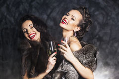 Rich women laughing with crystal of champagne Stock Images
