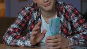 Rich young man counting euro banknotes, sitting home table, investment plan. Stock footage stock video