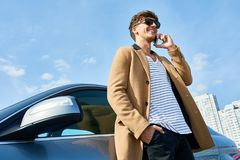 Rich Young Man Speaking by Phone in Sunlight. Low angle portrait of handsome young man speaking by phone standing in sunlight leaning on car outdoors against royalty free stock photo