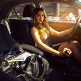Rich young girl driving car with bag full of money. Inside car photo royalty free stock photos