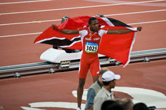 Richard Thompson celebrates with Trinidad flag. Richard Thompson takes a victory lap with American flag to celebrate his silver medal Royalty Free Stock Images