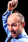 Riches. Man in a shirt and in a tie fills coins to itself on a head, on a black background Stock Photo