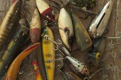 Richiami antichi di pesca sulla superficie approssimativa di legno osservata da sopra Fotografia Stock