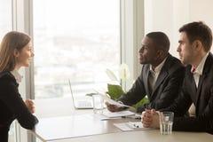 Richiedente femminile e reclutatori multirazziali durante l'intervista di lavoro Fotografie Stock Libere da Diritti