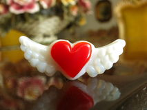 Richly colored red heart with wings on elegant table. Rich red glass heart with wings glass magnet on elegant mahogany dining room table Royalty Free Stock Image
