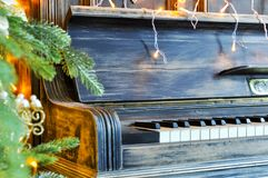 Richly decorated for Christmas with red and gold ornaments and lights on the background of an old piano. Elegant card. closeup. stock photo
