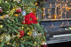 Richly decorated Christmas tree with red and gold ornaments and lights on the background of an old piano. Elegant card. closeup. stock photo