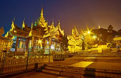 The gallery of Shwedagon Pagoda North Gate, Yangon, Myanmar. The richly decorated North Gate gallery with pyatthat roofs and carved decors, leading to the top of stock photos
