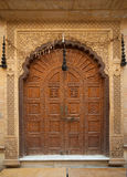 Richly detailed doors. A richly detailed carved doorway in the city of Jodhpur, Rajasthan, India. Carved stone framing and carved wooden doors Stock Image