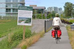 Richmond Canada and Development. A person cycles by a sign explaining the city of Richmond, Canada and their plans for development of the surrounding the area on Royalty Free Stock Photography