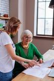 Richtende dame die op pensioen leningstoepassing met kleindochterhulp overweegt stock foto
