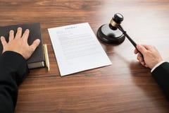 Richter, der den Hammer am Schreibtisch schlägt Stockbilder