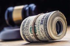 Richter ` s Hammerhammer Gerechtigkeitsdollarbanknoten und USA-Flagge im Hintergrund Gerichtshammer und gerollte Banknoten stockfotografie