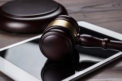 Richterhammer und -Tablet-Computer auf braunem hölzernem Stockbild
