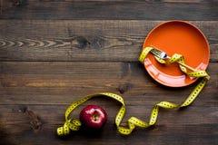 Richtige Nahrung für verlieren Gewicht Leere Platte, Apfel und messendes Band auf dunklem hölzernem Draufsicht-Kopienraum des Hin lizenzfreies stockfoto