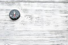 Richting en bewegingsconcept met omhoog kompas op witte houten achtergrond hoogste meningsspot royalty-vrije stock afbeeldingen