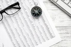Richting van beweging, bedrijfsrichting Kompas, glazen en documenten op bureau met toetsenbord witte houten stock fotografie