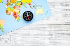 Richting van beweging, reisrichting Kompas en kaart op de grijze houten ruimte van het achtergrond hoogste meningsexemplaar stock foto