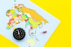 Richting van beweging, reisrichting Kompas en kaart op gele hoogste mening als achtergrond royalty-vrije stock foto