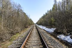 Richting van een enkelsporige spoorweg voor oude stoomtreinen of diesel treinen sporen en dwarsbalken in een mooi bos worden gele stock afbeeldingen