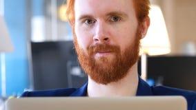 In Richtung der Kamera blicken, Mann, der im Büro arbeitet Stockfotografie