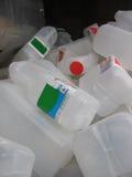 Riciclaggio dei contenitori del latte Fotografia Stock