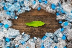 Riciclaggio del concetto Foglie verdi su un fondo di legno intorno alle bottiglie di plastica trasparenti Il problema di ecologia fotografia stock libera da diritti