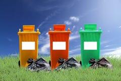 Ricicli i recipienti ed insacchi l'immondizia sul fondo dell'erba verde, l'ecologia Fotografie Stock