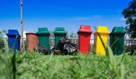Ricicli i secchi della spazzatura ed il sacchetto di plastica nero su erba Fotografia Stock