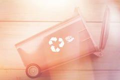 ricicli il bidone della spazzatura del recipiente con riciclano il logo sul vinta di legno del fondo Immagini Stock