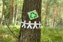 Ricicli il segno con gli uomini di carta su un albero Immagini Stock