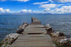 Rickety dock extends into blue sea beneath blue sky. Off the coast of the Mediterranean island of Corfu Greece Stock Photos