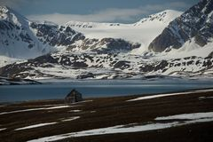Rickety hut in fjord with mountains behind Royalty Free Stock Image